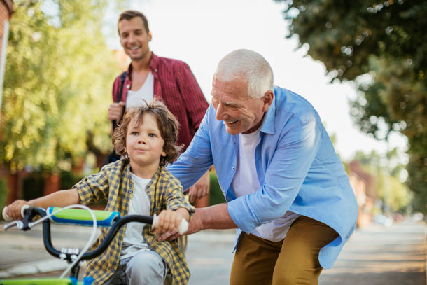 mature adult man with grandson riding tricycle