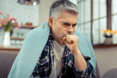 Man sitting, coughing, with blanket over his shoulders