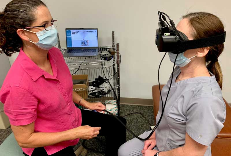 Healthcare staff person sitting, looking at patient with VR headset on